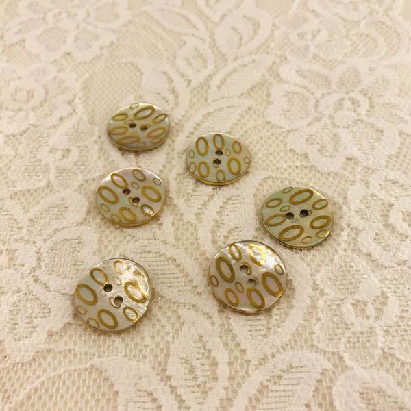 Knapp pärlemor mönster oval i guld naturvit